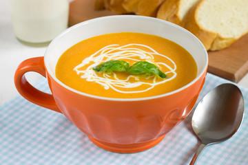 Tasty pumpkin soup with cream in orange bowl.