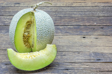 Green melon sliced on wooden table