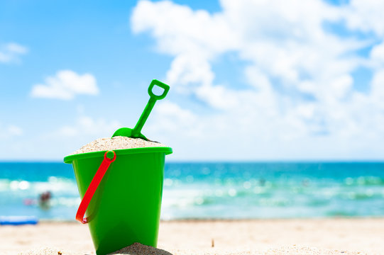 lone green child's beach toy sand bucket pail and shovel with sea and people playing in background