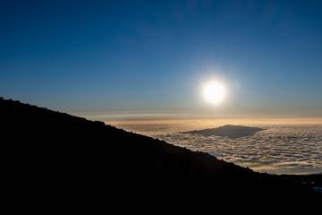 Hualalai peaks through the clouds as seen from the peak of Mauna Kea on the Big Island of Hawaii.