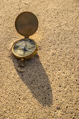 Antique compass on a sandy beach