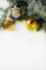 Christmas toy yellow balls and golden acorn on a branch. White w