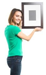 Woman hanging picture on white
