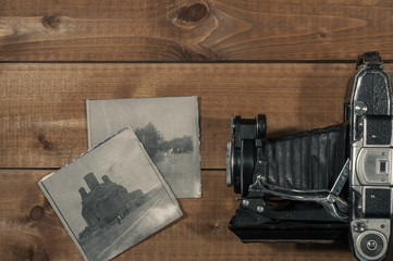 Old camera and black-and-white photos on the old wooden table