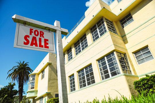 For Sale Sign with art deco condominium apartment building South Beach Miami Florida