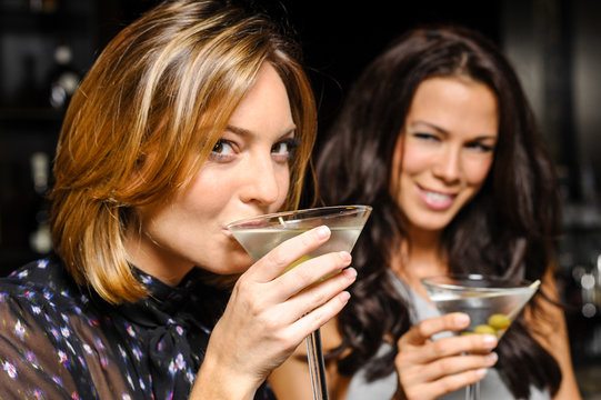 Two attractive young women drinking martinis in nightclub bar atmosphere