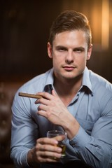 Man holding a cigar and glass of whisky in bar