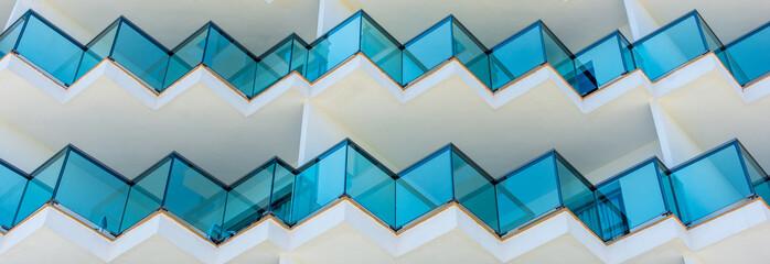 Fassade eines Hauses mit blau gefärbten Balkongeländern aus Glas