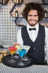 Bartender holding tray of cocktails and milkshake in bar