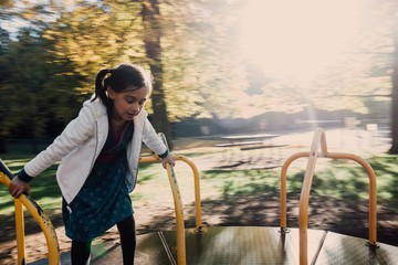 Girl Playing On Merry-Go-Round At Park
