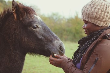 Smiling Woman Touching Horse On Field Against Sky