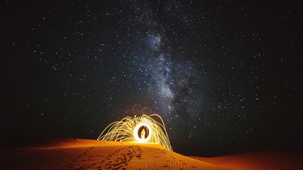 Person With Wire Wool On Field Against Starry Sky