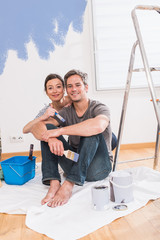 Handsome couple painting walls of their new home