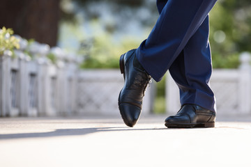 Man's feet in blue trousers and blue shoes