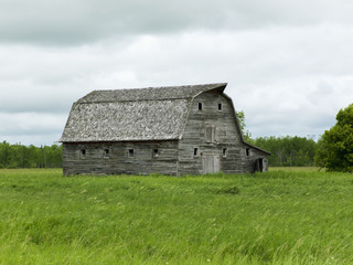 Old wooden barn in a grass field, Manitoba, Canada