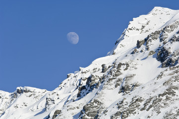 Moon Rising Over Snow Covered Mountain Peak At Hatcher Pass In Southcentral Alaska