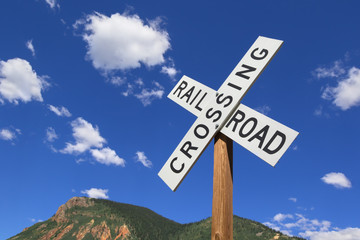 Railroad crossing sign with blue sky and mountains in Silverton, Colorado