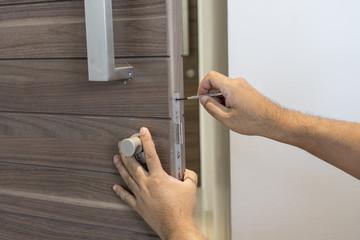 locksmith with screwdriver fix modern wood door