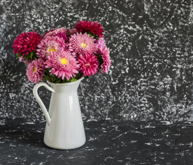 Bouquet of autumn flowers asters in a white jug on a dark background