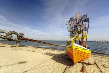 Drewniana,kolorowa łódź rybacka na plaży Morza Bałtyckiego