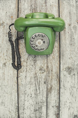 Old green telephone on an old table