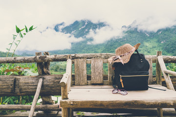 Travel backpack on the wooden bench with landscape