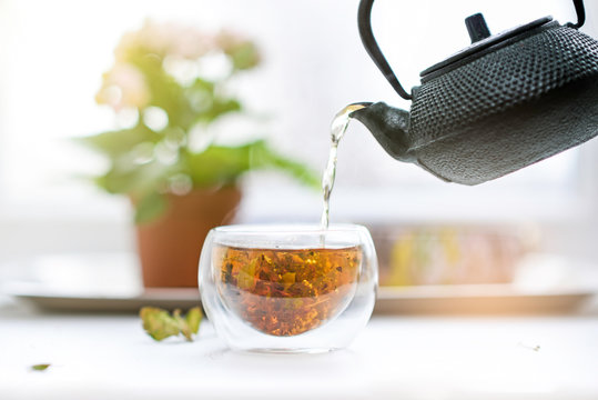 Herbal tea pouring from teapot to glass cup