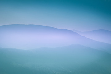 Landscape with colorful layers of mountains and haze in the valleys. The effect of color tinting.