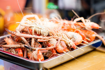 grilled shrimp in a tray on sale at a festival.