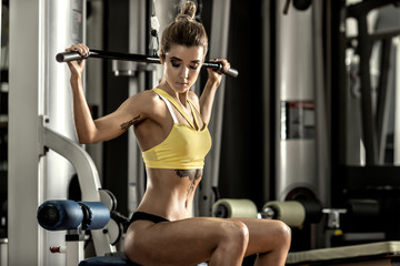 young fitness woman execute exercise with exercise-machine in gy