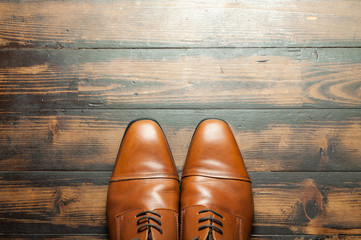 Men's leather shoes on a wooden floor