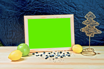 Christmas. Wooden empty photo frame with green chromakey. On the table scattered pearls. Lay lemon and apple. Christmas tree decoration. Blue background.