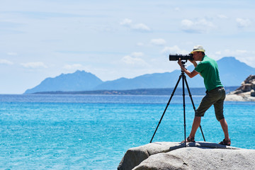 Photographer with tripod shooting sea landscape