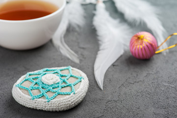 Cup of tea and crocheted pebble