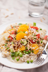 Hawaiian haystacks meal with chicken, sauce, brown rice, mandarin oranges, and other stacked vegetables