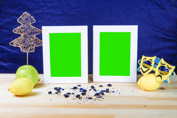Christmas. Two blank white photo frame with a green background. Theatrical masks. On the table scattered pearls. Lay lemon and apple. Christmas tree decoration. Blue background.