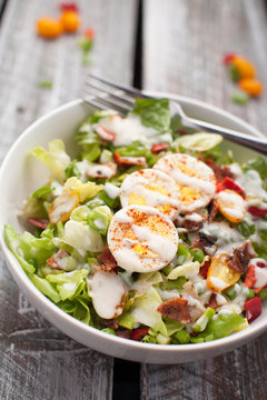 Fresh organic Cobb salad topped with homemade Ranch dressing, hard boiled eggs, bacon, peppers, peas, and green onions on an old weathered barn wood table