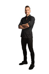 An attractive man in a black shirt and black jeans, standing against a white background smiling towards camera.