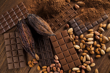 Chocolate bar, candy sweet, cacao beans and powder on wooden bac