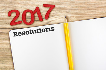 Top view of 2017 resolutions red number with blank open notebook