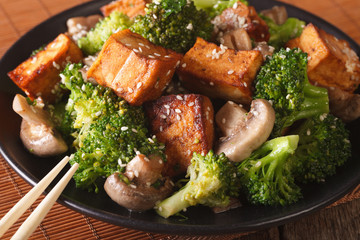 Vegetarian food: fried tofu with broccoli, mushrooms and sesame close-up. horizontal