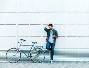 Young handsome guy with a bicycle leaning against the modern wall in the street. He is holding a mobile phone and looking at camera.