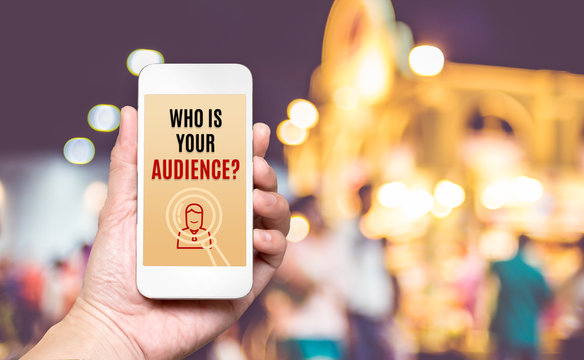 Hand holding mobile with Who is your audience? word on screen w