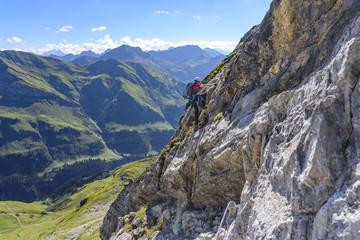 Jugendlicher klettert gesichert eine Felswand hinauf