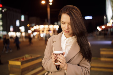 Portrait of woman in night city keep coffee cup