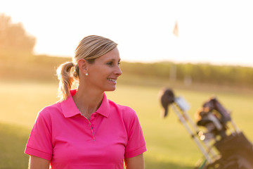 female Golfer portrait on sunset with flare