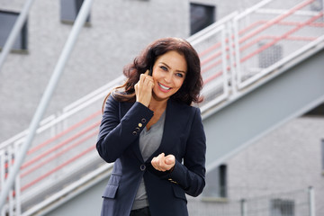 Smiling business woman outside on cellphone