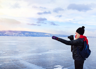 Woman tourist photographer is indicating something outside standing at frozen surface of lake Baikal. Winter tourism concept.