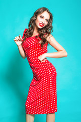 Beautiful brunette girl in a red dress on a blue background.