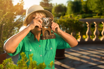 Mature woman holding camera. Lady in summer hat. What a wonderful view. Few photos of nature.